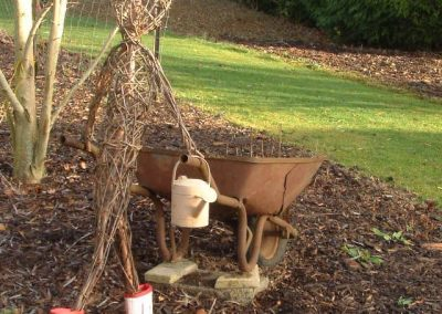 Woven willow figure with wheelbarrow at Willows Nursery. Woven willow bulrush decorations using corn dolly weave at Willows Nursery. Buy willow to make.